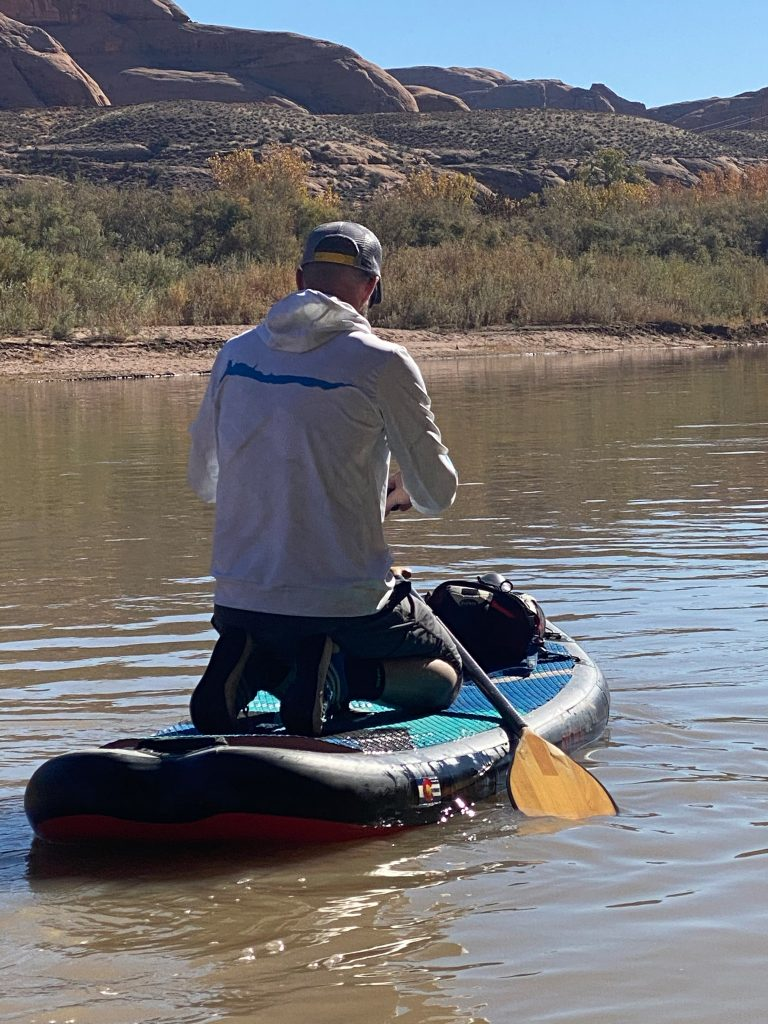 Honey Stinger Hive athleat Ricky Steamboat SUPing the Colorado river in Moab UT with the Hala Atcha SUP, Bending Branches carbon SUP paddle, and Kind Design's sweatshirt in ice.