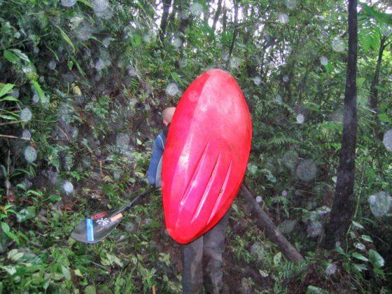 kayaker hiking through jungle